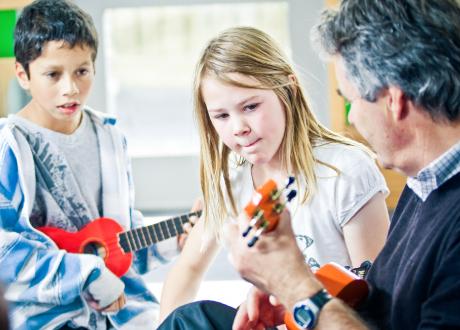 Two kids learning the ukulele